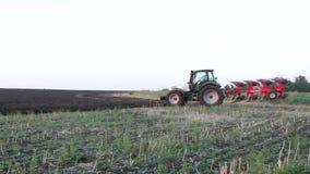 Traktor steht auf einem Gebiet der Schwarzerde bei Sonnenuntergang stock video footage