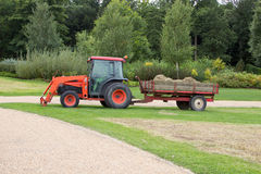 Traktor und caet mit Heu im Garten Lizenzfreie Stockbilder