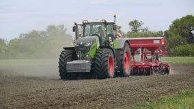 Traktor und Feld Ackerschlepper mit der Anhängersämaschine, die landwirtschaftliches Feld sät stock footage