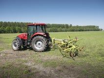 Traktor und Gras Turner funktionieren in der niederländischen Wiese in der Provinz von Südholland in den Niederlanden Lizenzfreie Stockbilder