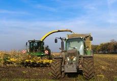 Traktor- und Maiserntemaschine auf dem Maisfeld Stockfotos