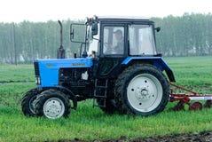 Traktorbetreiber pflügt den Standort im Regen Stockfotos