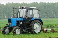 Traktorbetreiber pflügt den Standort im Regen Lizenzfreie Stockbilder