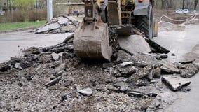 Traktoreimer bricht Asphalt stock footage