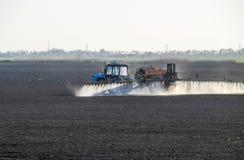 Traktoren besprutade växtbekämpningsmedel på fältet Kemi i agricu arkivbild