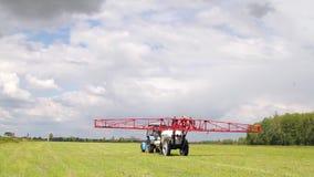 Traktoren besprutar ett fält med kemiska gödningsmedel för jordbruk stock video