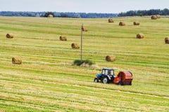 Traktoren drar den runda baleren i bakgrunden av ett fält royaltyfri foto