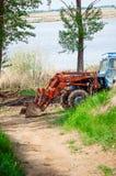 Traktoren gräver jorden på flodbanken Ryssland arkivfoton