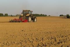 Traktoren i fältet på jordbruks- operationer Royaltyfria Foton