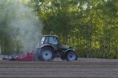 Traktoren i fältet på jordbruks- operationer Royaltyfri Foto