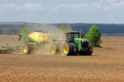 Traktoren John Deere producerar kornskördar arkivfoton