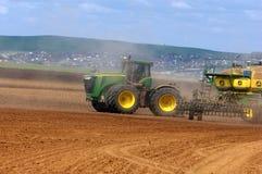 Traktoren John Deere producerar kornskördar arkivbild
