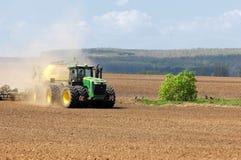 Traktoren John Deere producerar kornskördar arkivbilder