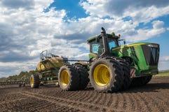 Traktoren John Deere producerar kornskördar royaltyfria foton