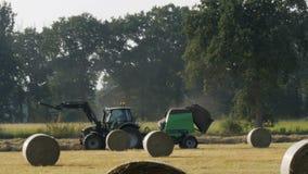 Traktoren kör på fältet i nedgången och samlar hö i baler arkivfilmer