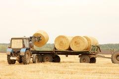 Traktoren lastar av baler av hö i fältet Royaltyfria Foton