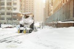 Traktoren med borste- och skopalokalvård snöar på stadsgatan och parkering efter tungt snöfall på vintern royaltyfria bilder