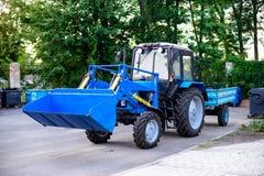 traktoren med släpet för att göra ren parkerar territorier Arkivbilder
