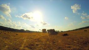 Traktoren och skördetröskan lämnar fältet efter jordbruks- arbete lager videofilmer