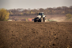 traktoren på stora hjul odlar lönelyfter dammar av på plöjd jord Arkivfoto