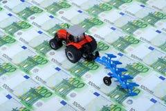 Traktoren plöjer och Euros Royaltyfria Bilder