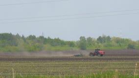 Traktoren plogar eller harvar jordningen p? f?ltet arkivfilmer