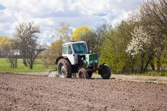 Traktoren plogar en täppa av land Arkivbilder