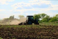 Traktoren plogar ett fält Arkivbild