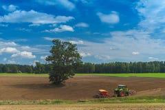 Traktoren plogar fältet Landskap i land Arkivbilder