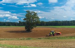 Traktoren plogar fältet Landskap i land Royaltyfri Foto