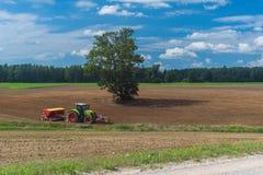 Traktoren plogar fältet Landskap i land Royaltyfri Bild
