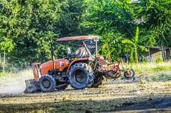 Traktoren plogar för att justera området för fält och att parkera för fotboll abstrakt blur Royaltyfri Bild