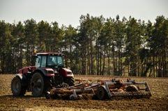 Traktoren plogar f?ltet V?r b?rjan av den plantera s?songen Stora traktorritter p? f?ltet arkivbild