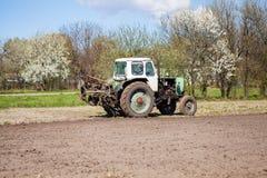 Traktoren plogar jorden Arkivfoton