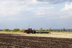 Traktoren plogar jorden arkivbild