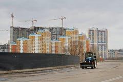 Traktoren rider på vägen mot bakgrunden av bostads- byggnader under konstruktion i Moskva Royaltyfri Foto
