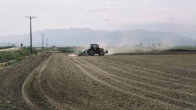 Traktoren som plogar ett dammigt fält med folk, ser royaltyfria foton