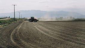 Traktoren som plogar ett dammigt fält med folk, ser arkivfoto