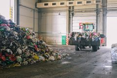 Traktoren transporterar avskräde på växten för att bearbeta och att sortera avfalls Lyftt bulldozerhink med avfalls Hög av avfall arkivfoton
