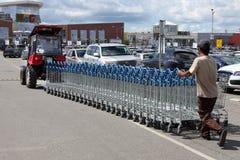 Traktoren Vitryssland drar en rad av shoppingvagnar i den MEGA supermarket, Moskva Royaltyfria Bilder