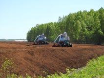 Traktorer som arbetar i träsk Royaltyfri Bild