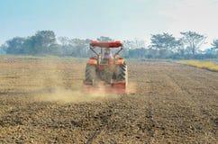 Traktorer som planterar lantgårdfältet Arkivfoto