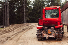 Traktorhätta och stora hjul på den naturliga jordvägen i vårskog Fotografering för Bildbyråer