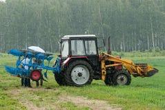 Traktoroperatören plogar platsen i regn Tyumen Arkivbild