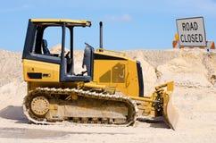 Traktorplanierraupe, die an Straßenbau arbeitet Lizenzfreie Stockfotos