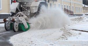 Traktorreinigungsschnee Ausblasen des Schneepulvers von der Schneeräumung Lizenzfreie Stockfotos