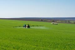 Traktorsprühschädlingsbekämpfungsmittel auf einem Gebiet des Weizens stockfoto