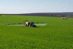 Traktorsprühschädlingsbekämpfungsmittel auf einem Gebiet des Weizens lizenzfreie stockfotos