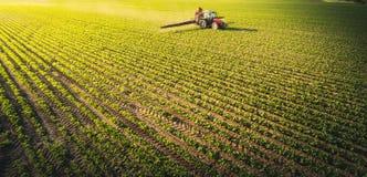 Traktorsprühsojabohnenfeld am Frühling lizenzfreie stockfotografie