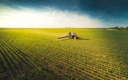Traktorsprühsojabohnenfeld am Frühling stockfoto